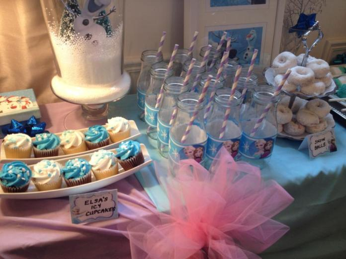 "To save time, I just picked up store bought cupcakes in ""Frozen"" colours, and the glass bottles were collected while on vacation in Florida. The Targets in the US sell Starbucks frappuccinos in the small glass bottles, so we loaded up on 4 cases. I washed them all (after enjoying a yummy frappuccino), and removed the labels. Now, whenever we have a party, I can print out labels for whatever theme, and re-use them, as they were only attached with a piece of tape. A pretty paper straw completes the theme. They are also super handy, as I wrote each child's name on the paper label, so everyone knew which one belonged to them."